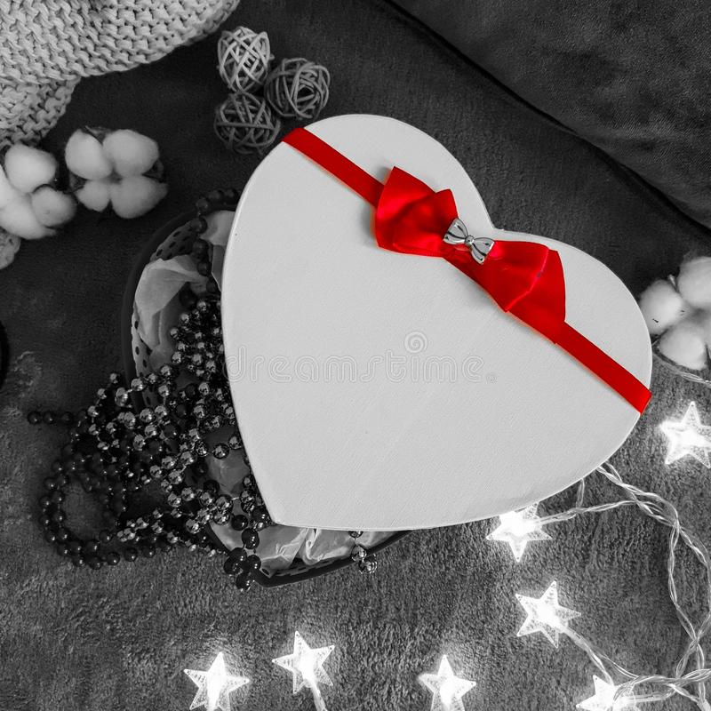 Romantic black and white layout with a heart-shaped gift, a glowing garland and a bright scarlet ribbon with a bow royalty free stock photography