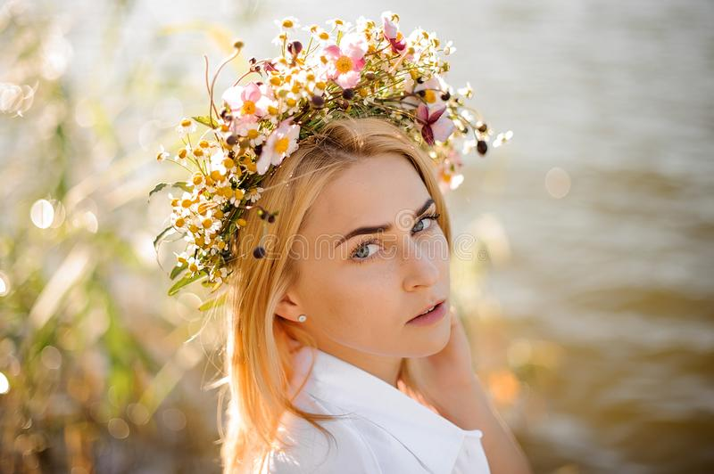 Romantic blond girl in a wreath of flowers royalty free stock photo