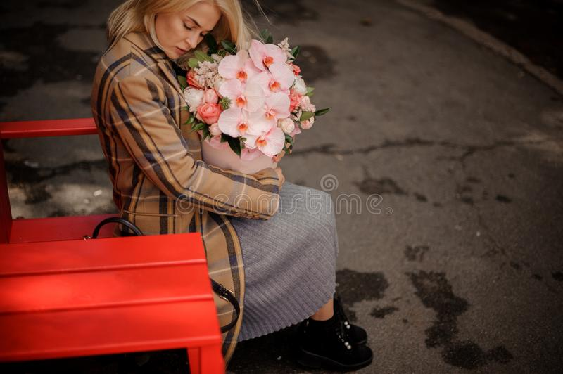 Romantic blonde woman sitting on a red chair near the street cafe with a box of flowers royalty free stock photos