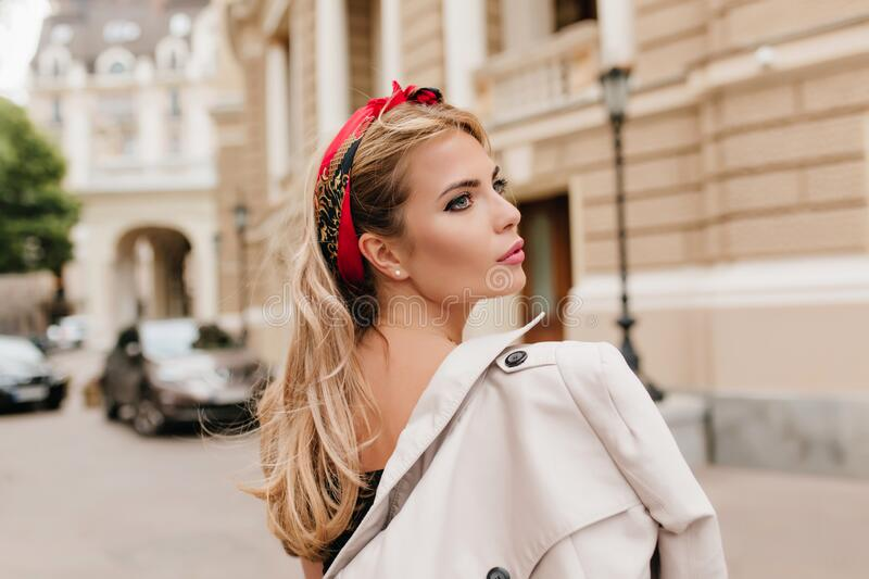 Romantic blue-eyed girl carrying coat on shoulder and looking away. Pensive blonde young woman spending time in city and royalty free stock photography
