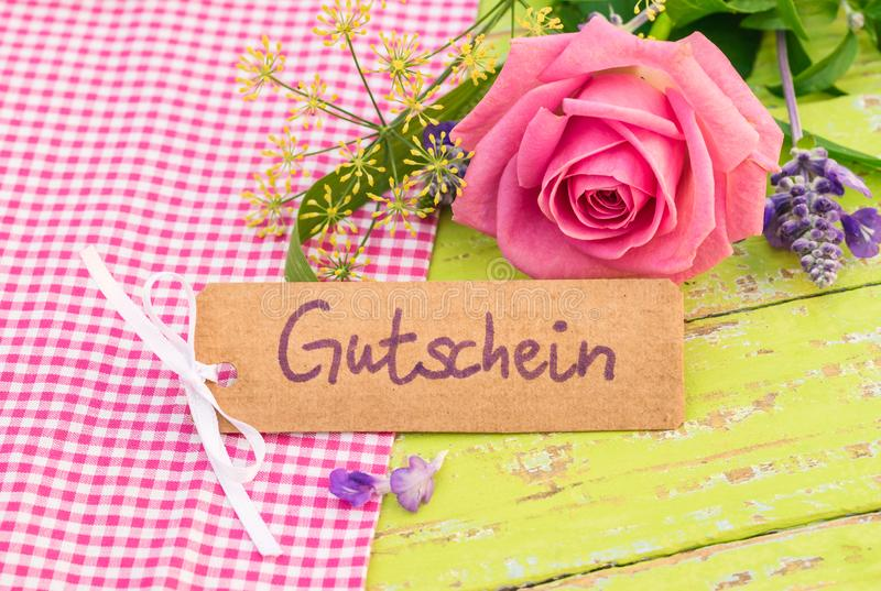 Romantic bunch of flowers and gift card with german word, Gutschein, means voucher or coupon royalty free stock images