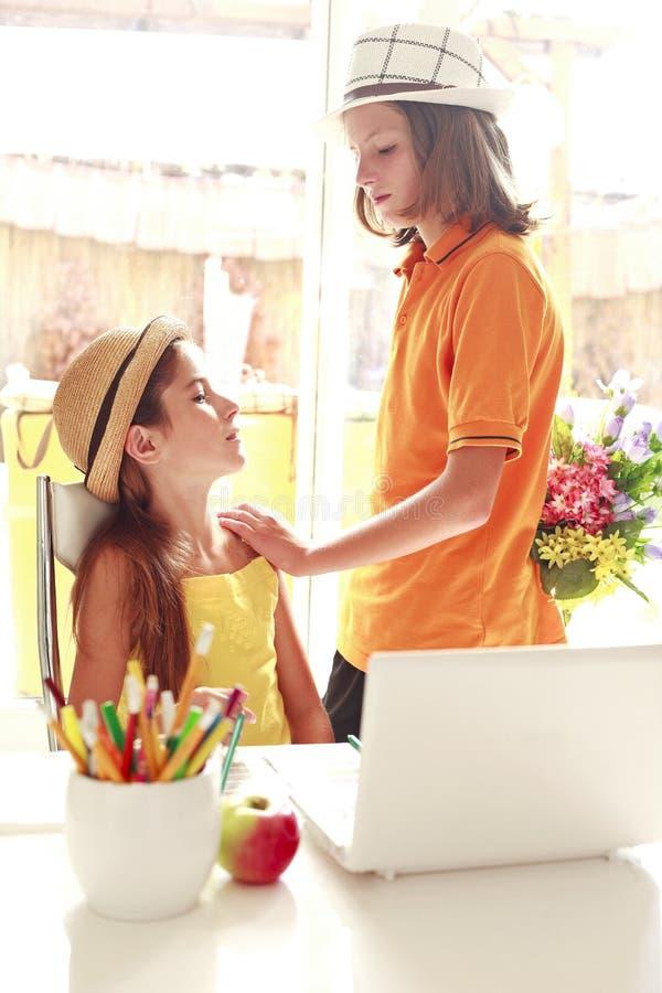 Romantic boy giving flowers to beautiful girl stock photos