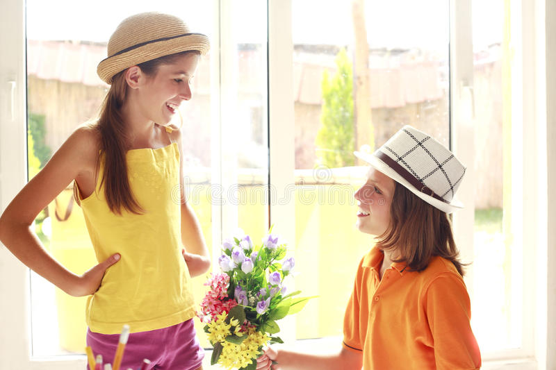 Romantic boy giving flowers to beautiful girl royalty free stock image