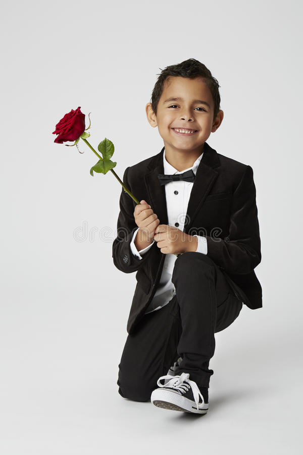 Romantic boy proposing. Young boy kneeling with romantic red rose royalty free stock image