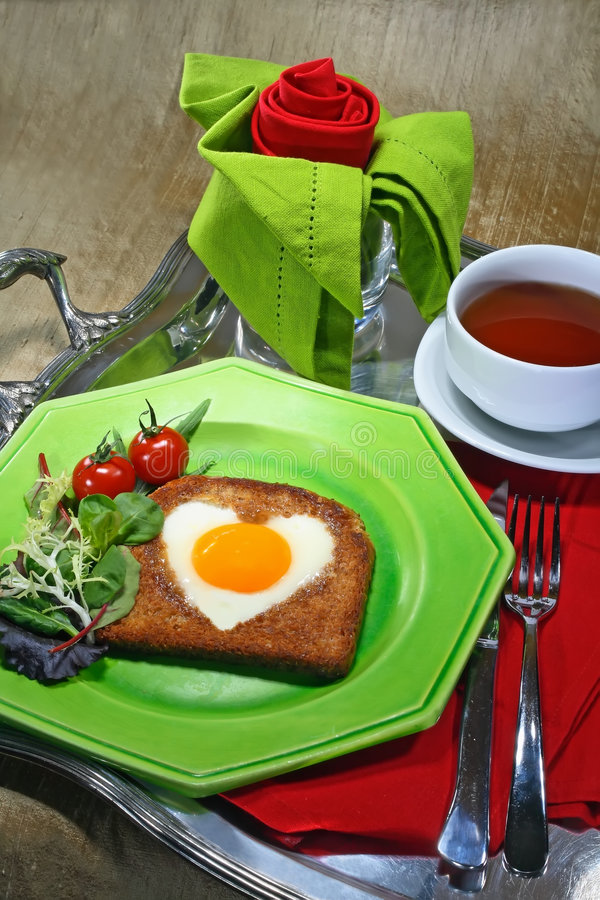Romantic breakfast. Breakfast tray with fried egg in the shape of a heart, a cup of tea and a napkin folded as a rose stock image