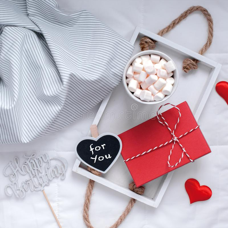 Romantic breakfast in bed. Birthday concept. Square Top view flat lay sill life romantic composition. Hot cacao coffee chocolate with marshmallows mug red gift royalty free stock images