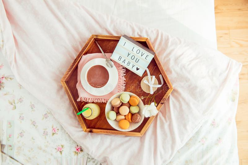 Romantic Breakfast in bed with I love you baby text on lighted box. Cup of coffee, juice, macaroons, flower and gift box on wooden. Tray. Birthday, Valentine`s stock image