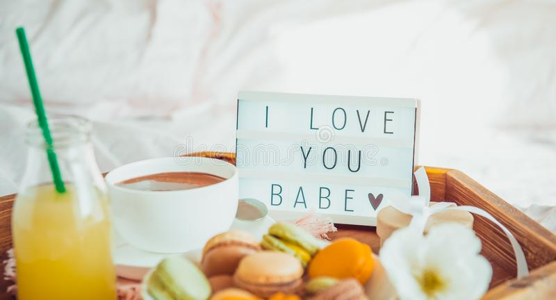 Romantic Breakfast in bed with I love you baby text on lighted box. Cup of coffee, juice, macaroons, flower and gift box on wooden. Tray. Birthday, Valentine`s stock photo