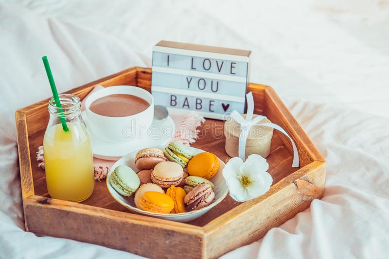 Romantic Breakfast in bed with I love you baby text on lighted box. Cup of coffee, juice, macaroons, flower and gift box on wooden. Tray. Birthday, Valentine`s stock photography