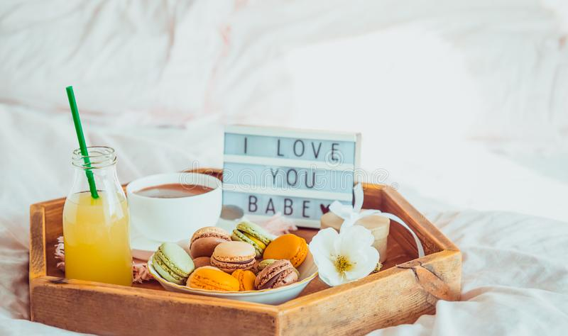 Romantic Breakfast in bed with I love you baby text on lighted box. Cup of coffee, juice, macaroons, flower and gift box on wooden. Tray. Birthday, Valentine`s royalty free stock photo