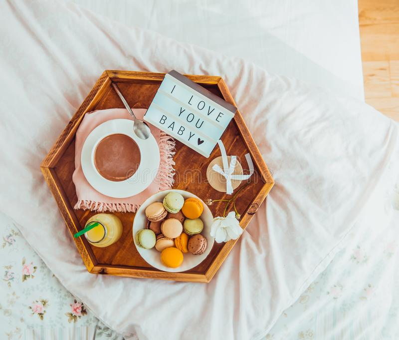 Romantic Breakfast in bed with I love you baby text on lighted box. Cup of coffee, juice, macaroons, flower and gift box on wooden. Tray. Birthday, Valentine`s royalty free stock photos