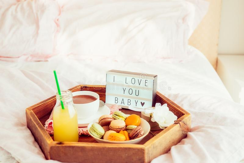 Romantic Breakfast in bed with I love you baby text on lighted box. Cup of coffee, juice, macaroons, flower and gift box on wooden. Tray. Birthday, Valentine`s stock images