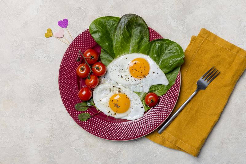 Romantic breakfast with fried eggs at red plate on white background stock photo