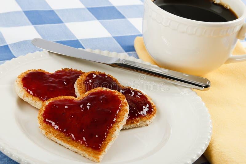 A romantic breakfast treat. Three heart-shaped toasts coated with raspberry jam make a romantic Valentine breakfast royalty free stock photos