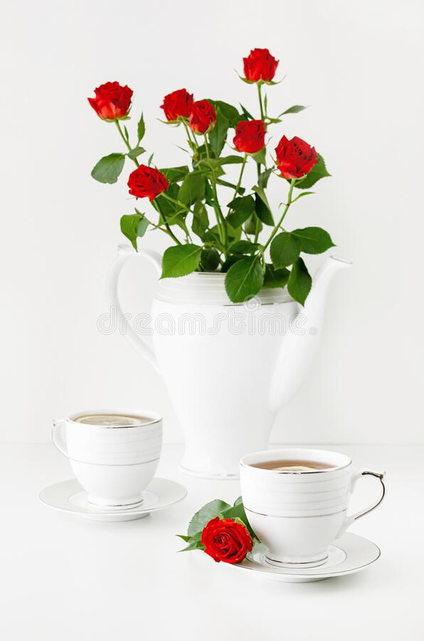 Romantic breakfast for two on a Valentines day with tea and bouquet of red roses. Love greeting card. Concept stock image