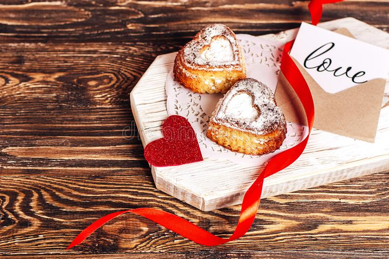 Romantic breakfast for Valentine`s Day. Two homemade cupcakes in the form of a heart, a red ribbon, a card with the inscription royalty free stock image