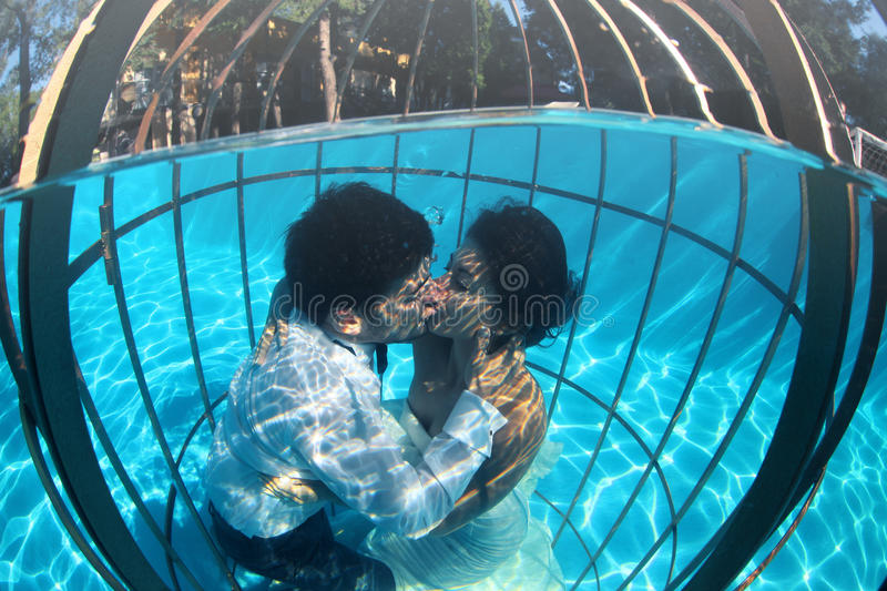Romantic Bride And Groom Underwater In A Bird Cage Stock Photo