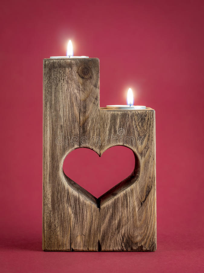 Romantic candle holder. Lit romantic wooden candle holder with cut heart over red background royalty free stock photo