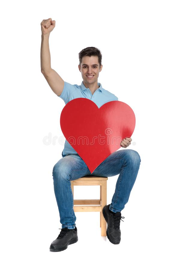 Romantic casual guy celebrating and holding a heart shape. Romantic casual guy celebrating with his fist in the air and holding a heart shape while smiling and royalty free stock images