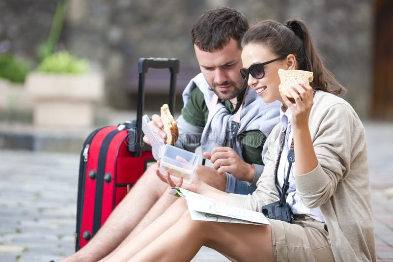 Romantic Caucasian Couple Traveling Around City. Sitting on Floor With Luggage and Having Lunch with Sandwiches royalty free stock photos
