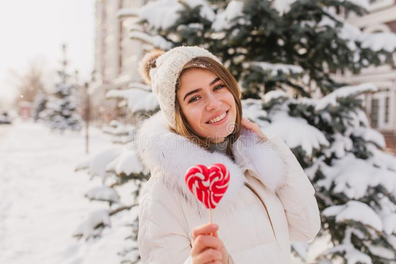 Romantic caucasian woman in white attire eating candy during winter outdoor photoshoot. Photo of pretty blonde girl in stock images