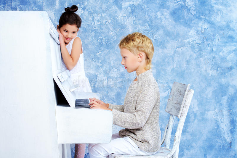 Romantic children. Playing the white piano. Music and art concept. Vintage, retro style royalty free stock photo