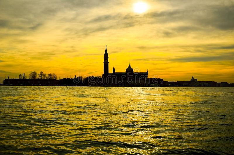 Old ancient tower of church complex in the middle of water during orange sunset stock images