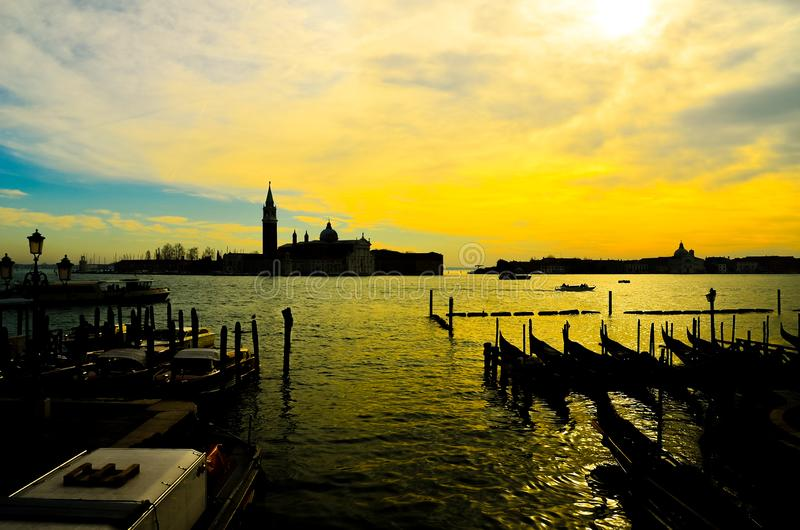 Old ancient tower of church complex in the middle of water during orange sunset stock photo