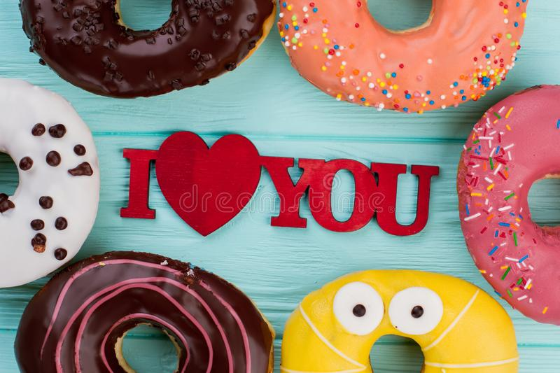 Romantic composition with assorted donuts. Various glazed donuts and inscription I love you. Happy Valentines Day stock image