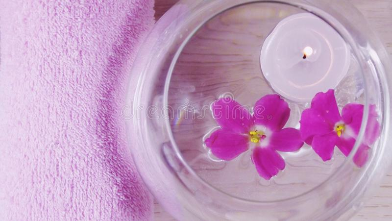 Romantic composition with a candle and violet flowers floating in a bowl of water. The concept of Spa,cosmetic,procedure,treatment royalty free stock photos