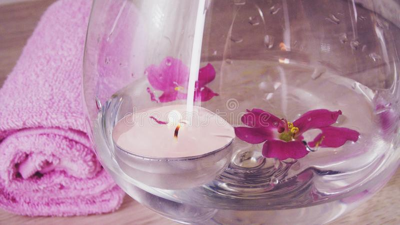 Romantic composition with a candle and violet flowers floating in a bowl of water. royalty free stock photo