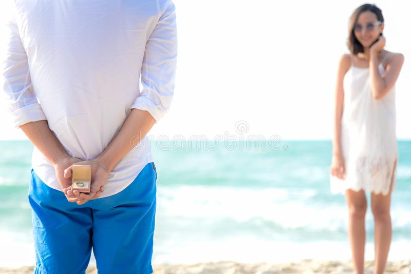 Romantic concept with man holding white ring making marriage proposal in the beach. Asian couple lover honeymoon at luxury reso royalty free stock image