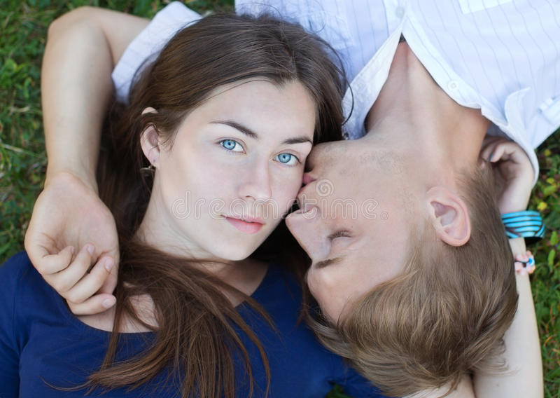 Romantic couple. Romantic happy young couple in love relaxing on the grass royalty free stock photography