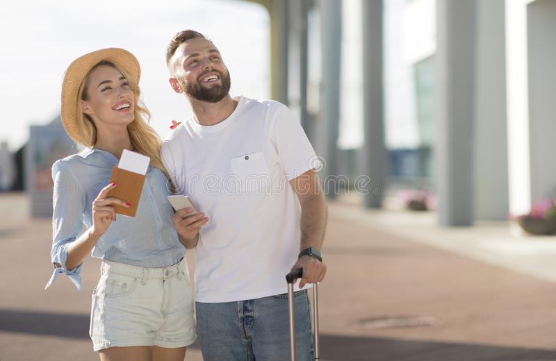 Romantic couple arriving at airport and looking aside stock photography