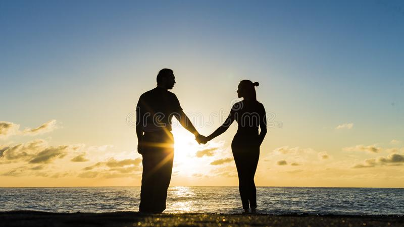 Romantic couple on the beach at colorful sunset on background stock image