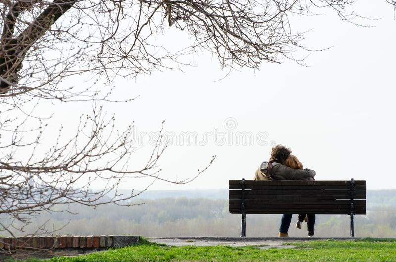 Romantic couple on bench stock images