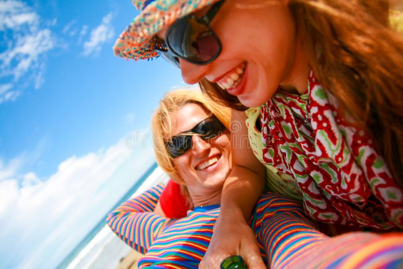Romantic couple with happy smiling faces in colourful outfit and sunglasses enjoying holiday on the sun royalty free stock photos