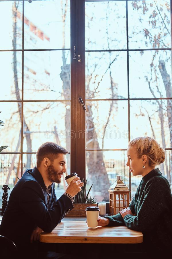 Romantic couple in the cafe is drinking coffee and talking. Handsome men and beautiful girl enjoying being together stock photos