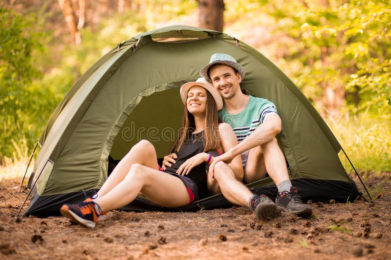 Romantic couple camping outdoors and sitting in tent. Happy Man and woman on camping vacation. stock photography
