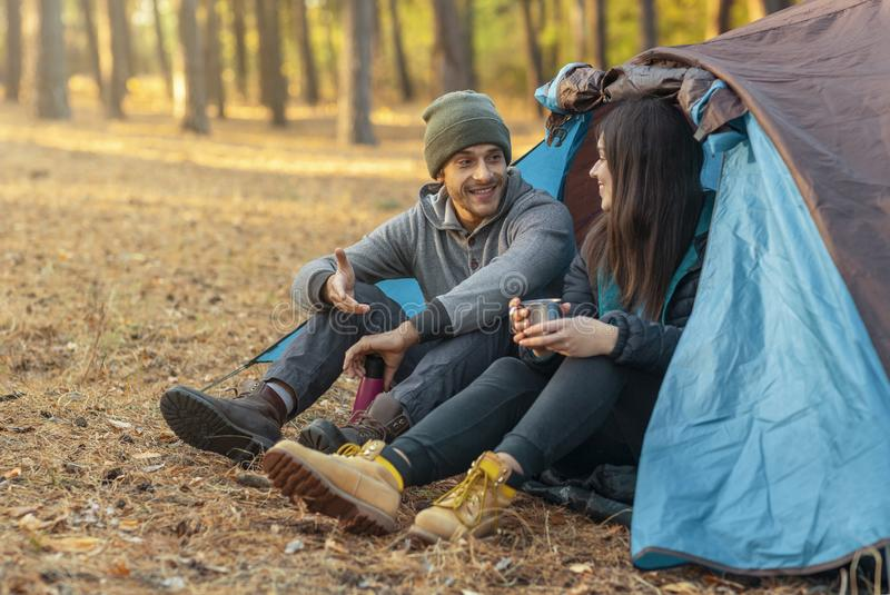 Romantic couple camping outdoors, sitting in tent royalty free stock photography