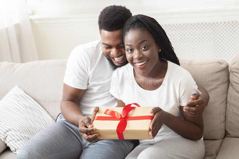 Romantic couple cuddling and holding gift box while sitting on couch at home stock image