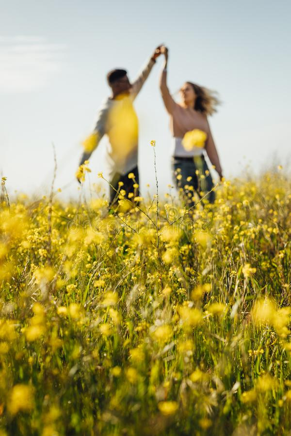 Romantic couple dancing in meadow of yellow flowers royalty free stock photography