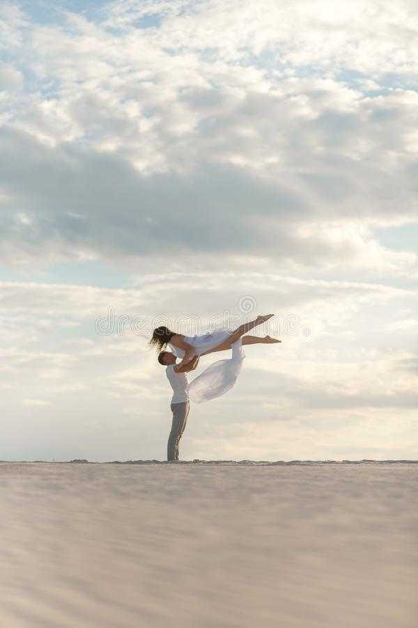 Romantic couple dancing in sand desert. The guy lifts the girl above himself. Sunset sky stock photo