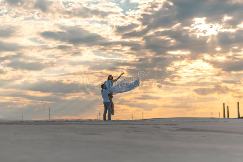 Romantic couple dancing in sand desert. The guy lifts the girl above himself. Sunset sky.  royalty free stock images