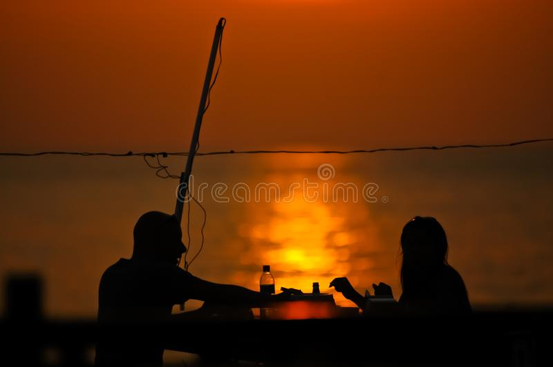 Romantic couple dating at sun set. Sitting together and having a conversation near the sea stock image