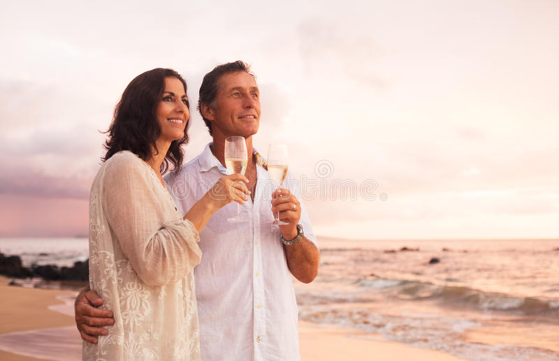 Romantic Couple Drinking Champagne on the Beach at Sunset stock photography