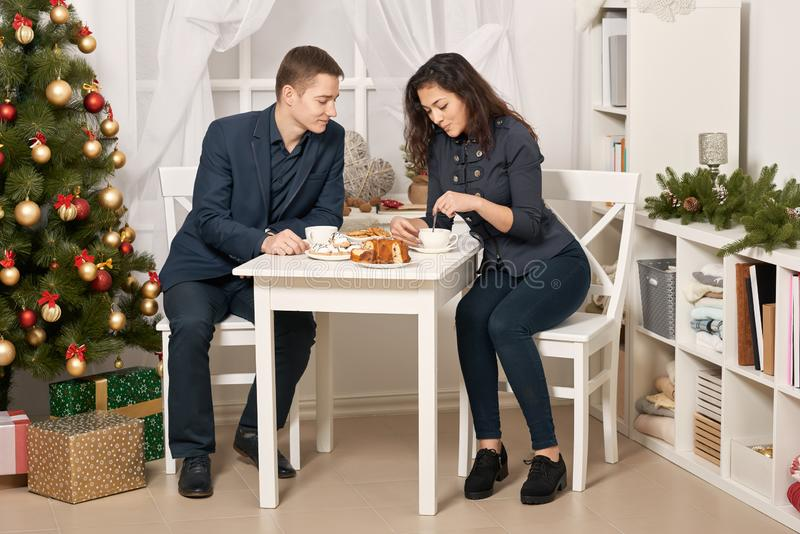 Romantic couple drinking tea with cookies and talking, christmas tree with holiday decoration, new year theme royalty free stock images
