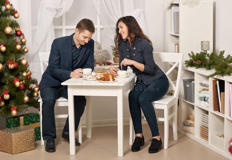 Romantic couple drinking tea with cookies and talking, christmas tree with holiday decoration, new year theme stock photo