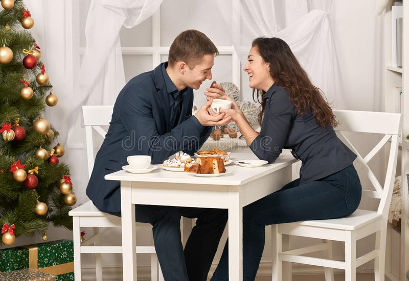 Romantic couple drinking tea with cookies and talking, christmas tree with holiday decoration, new year theme royalty free stock photo