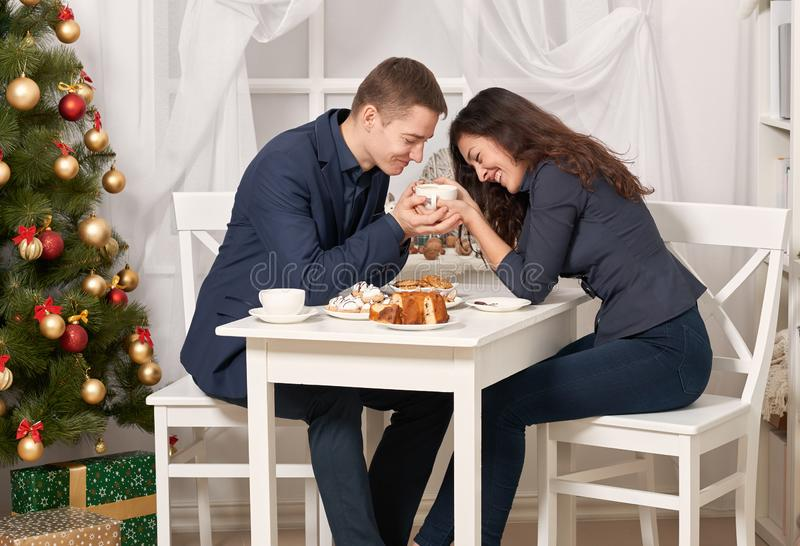 Romantic couple drinking tea with cookies and talking, christmas tree with holiday decoration, new year theme royalty free stock photography
